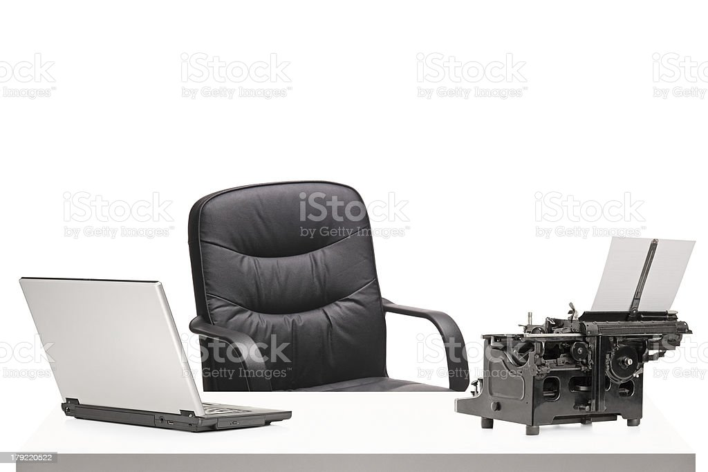 Laptop and an old fashioned typing machine on a table royalty-free stock photo