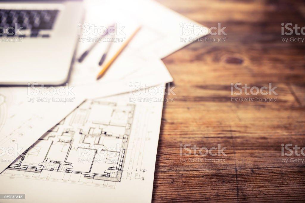 Laptop und Architekturpläne auf einem Schreibtisch aus Holz – Foto