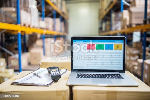 Laptop, barcode scanner, clipboard with notes and pen on the top of boxes in a warehouse.