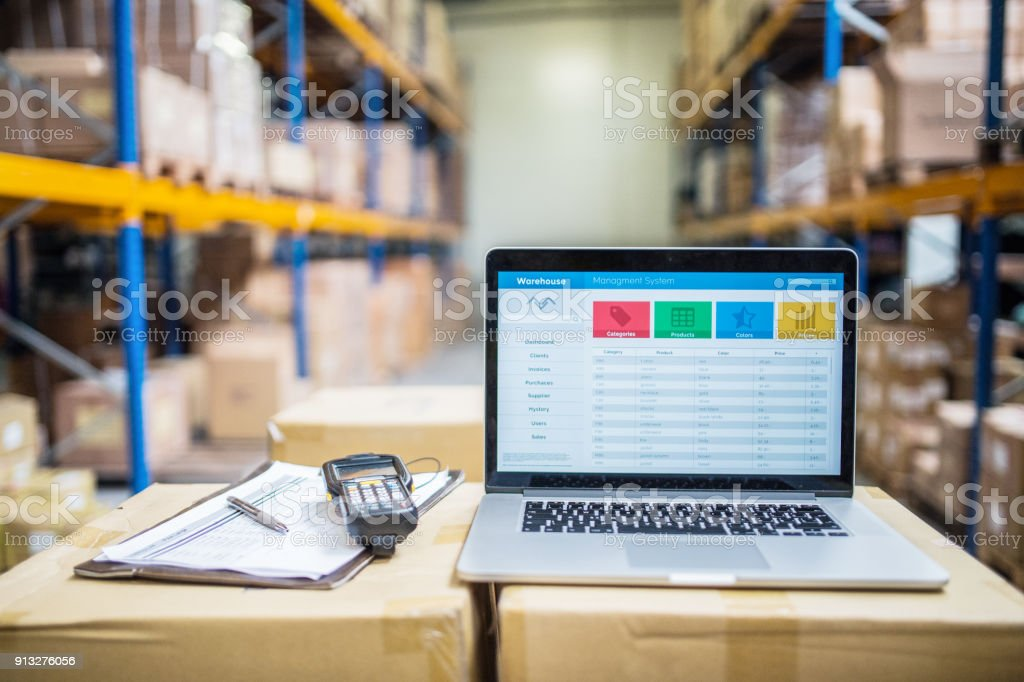 Laptop and barcode scanner on boxes in a warehouse. stock photo