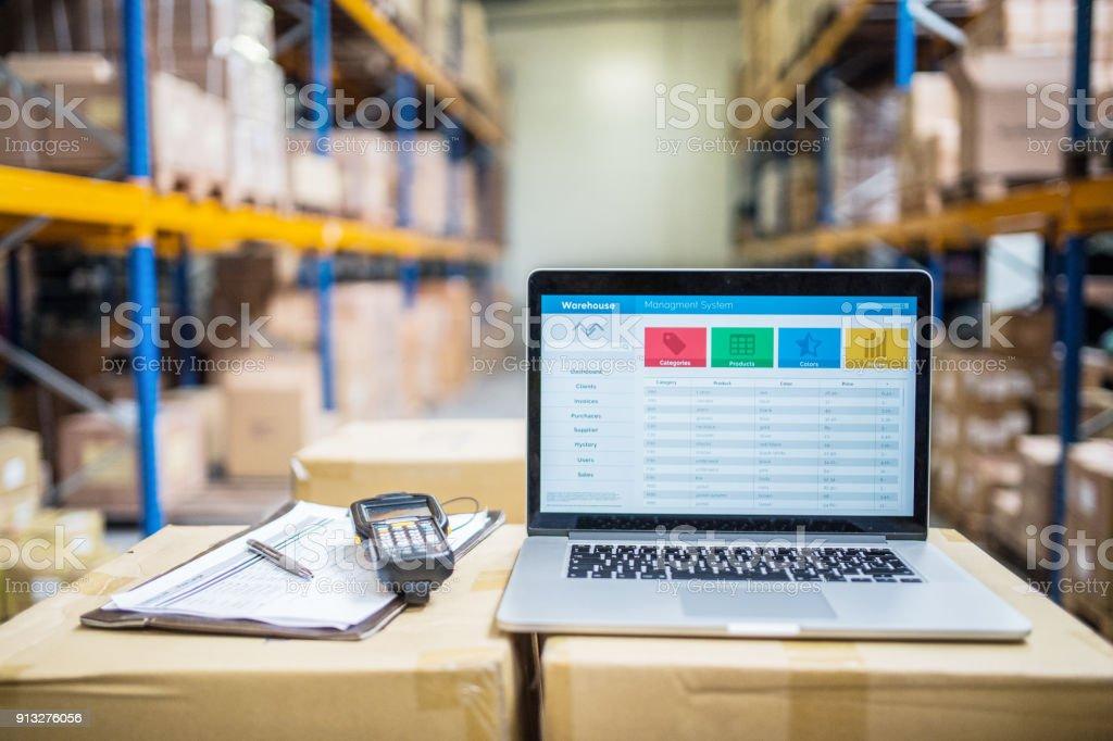 Laptop und Barcode Scanner auf Boxen in einem Lagerhaus. – Foto