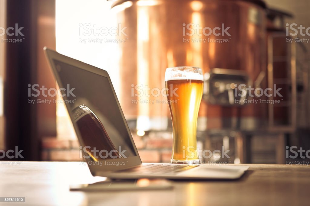 Laptop and beer pint glass in table at micro brewery Open laptop and beer pint glass in table at micro brewery with copper vat in background. Alcohol - Drink Stock Photo