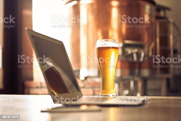 Laptop And Beer Pint Glass In Table At Micro Brewery Stock Photo - Download Image Now