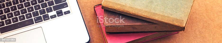 istock laptop and books, in wooden background 991001984
