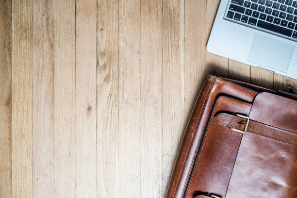 Laptop and Briefcase on a desk from above. stock photo