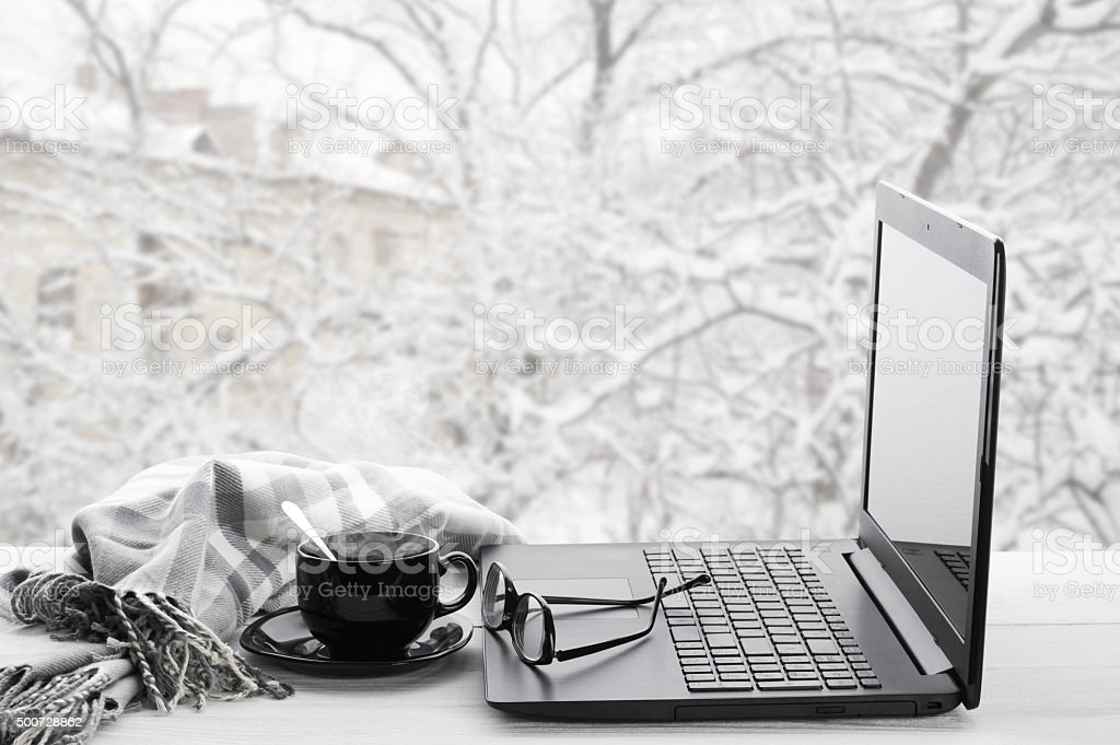 Laptop and coffee on winter window stock photo