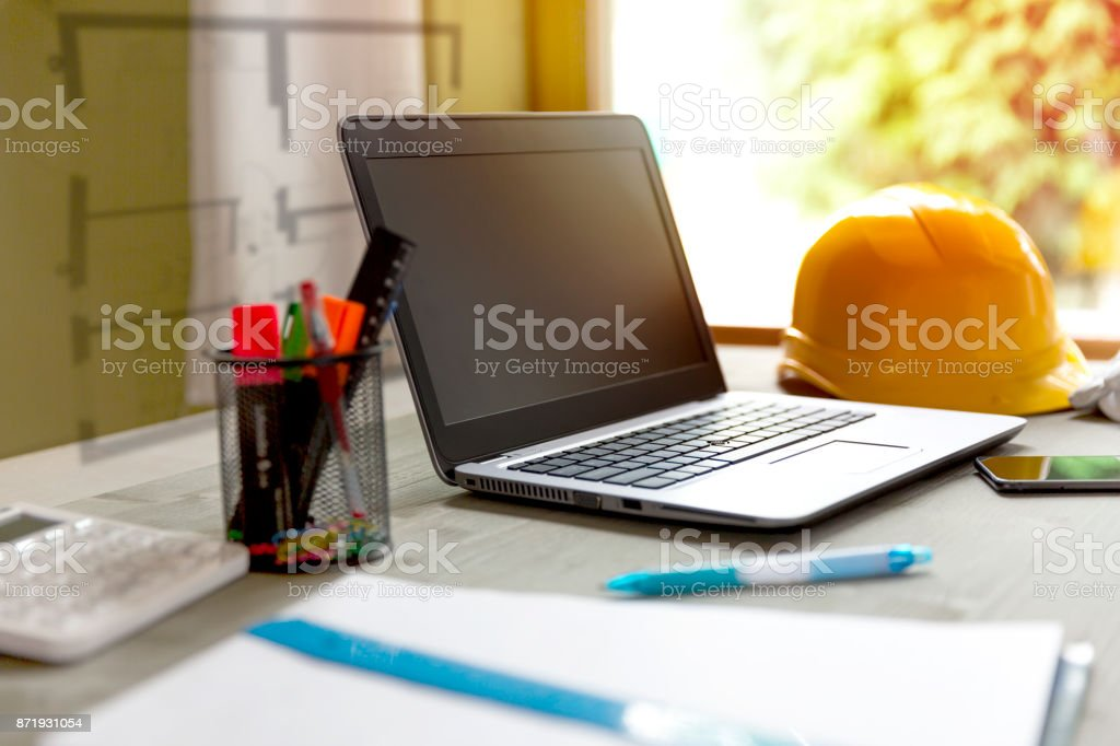 Laptop and contractors helmet in designers/architects office stock photo