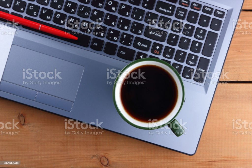 Laptop and cup of coffee on a wooden background, old desk, smartphone...