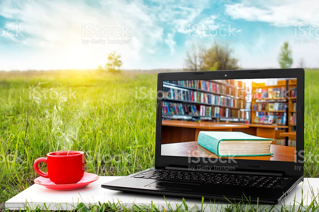 Laptop and cup of hot coffee. E-book library concept.Business ideas. stock photo