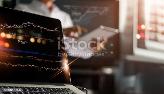 istock Laptop and data stock market on screen. Businessman using tablet and analyzing stock exchange online in monitoring room background, forex trading graph, stock market and financial investment concept. All on laptop screen are design up. 1069541600