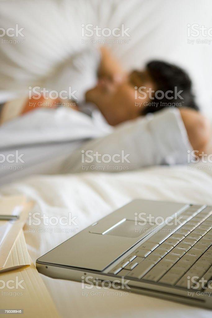 Laptop und Mann Schlafen auf dem Bett Lizenzfreies stock-foto