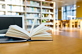 istock Laptop and open book on the table of public library 1193279839