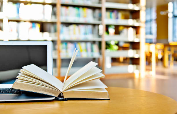 Laptop and open book on the table of public library stock photo