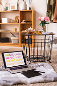 Laptop and pad with stylus on plaid by small table with herbal tea and pink roses standing on the floor with bookshelf on background