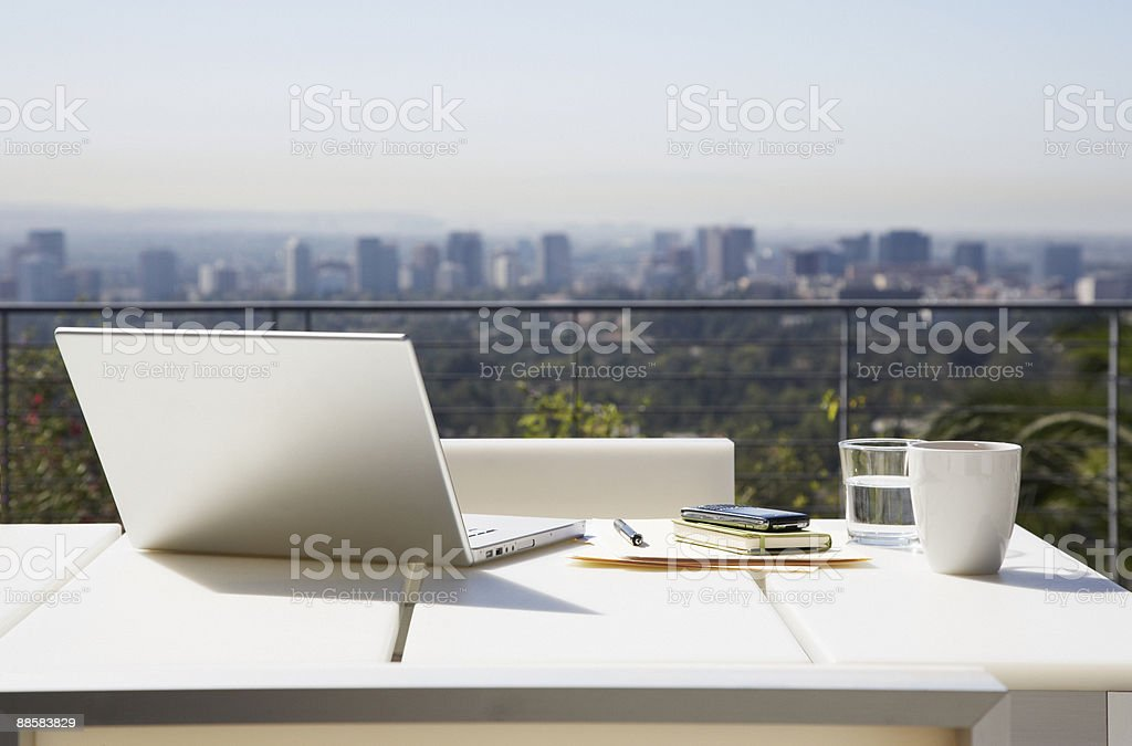 Laptop and paperwork on balcony table stock photo