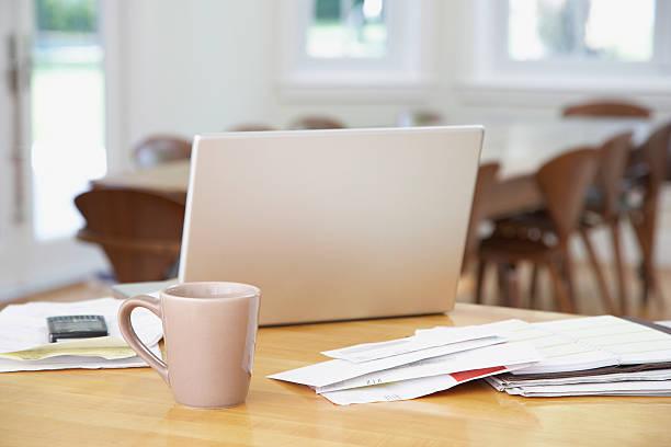 laptop and paperwork on kitchen counter with mug - 虛擬辦公室 個照片及圖片檔