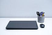 istock Laptop and pen holder on white desktop 1323988089