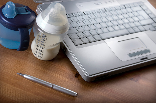 Laptop And Pen Next To Baby Bottle And Toddler Cup Stock Photo - Download Image Now
