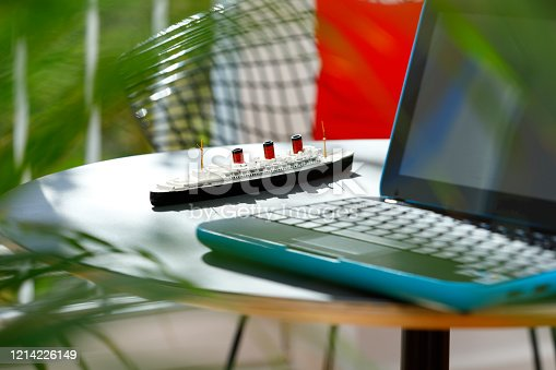 Laptop and metal miniature model of a historical cruise ship on a coffee table
