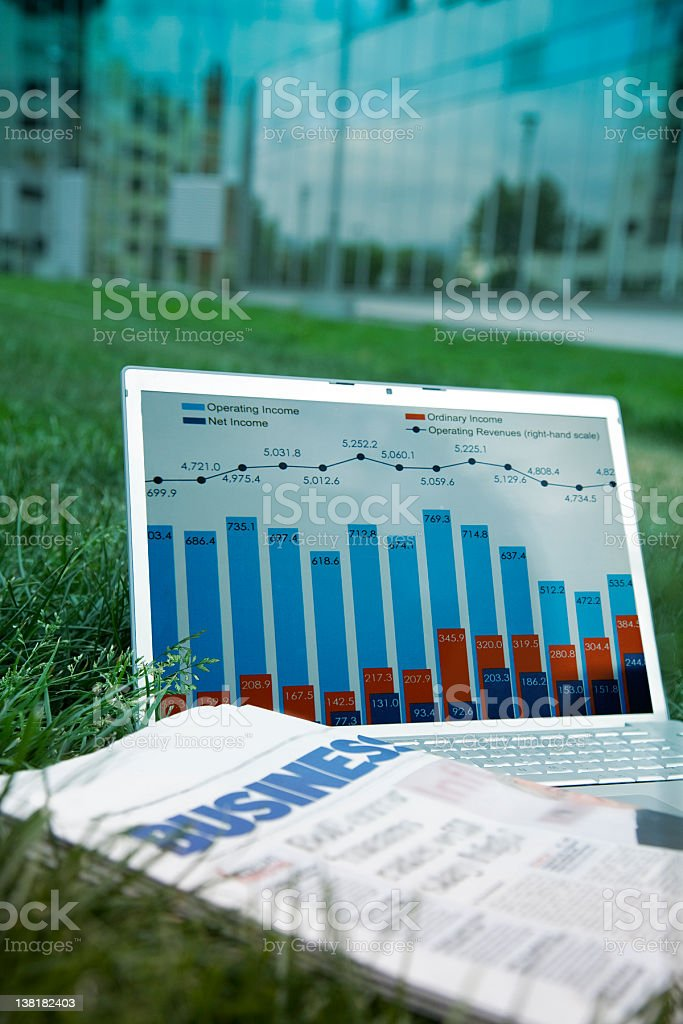 Laptop, business paper, grass outside office building royalty-free stock photo