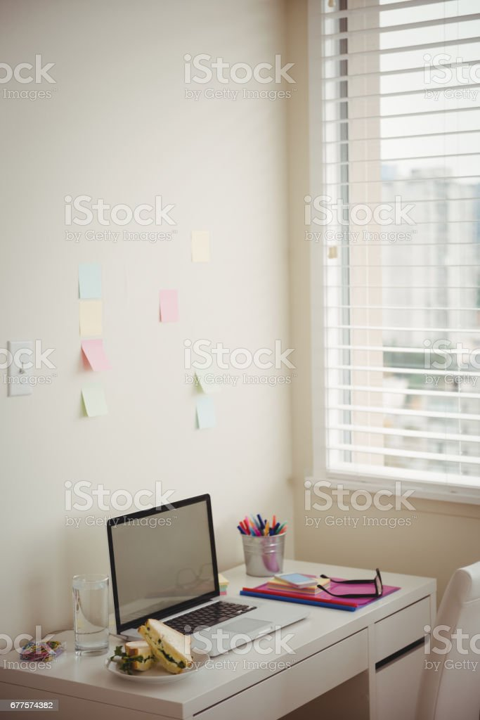 Laptop by food and office supplies on table royalty-free stock photo