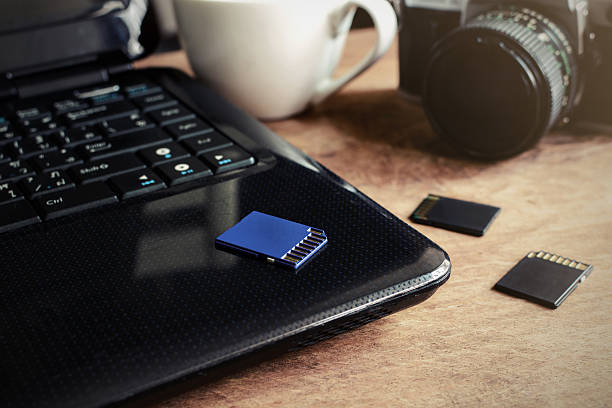 laptop, camera and a cup of coffee on wooden desk - memory card stock photos and pictures
