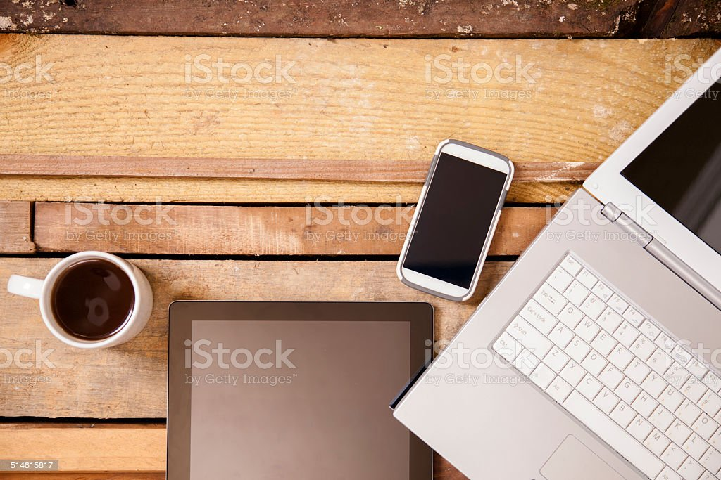 Laptop, cell phone, coffee, digital tablet on wooden table. Nobody. stock photo