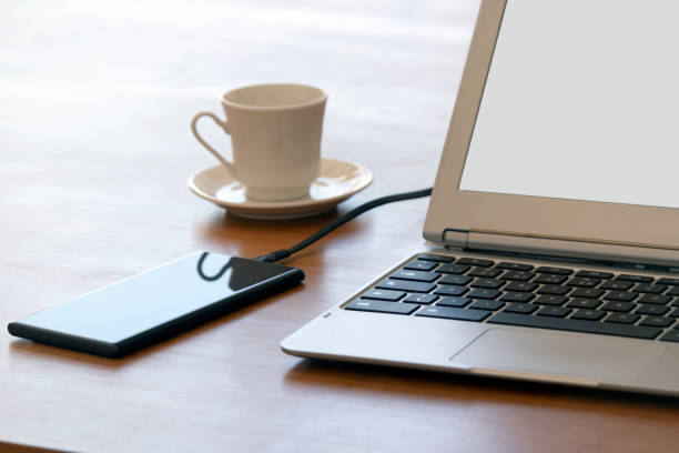 Laptop charging a mobile phone. Photo of a mobile being charged with a laptop over a wooden table. external hard disk drive stock pictures, royalty-free photos & images