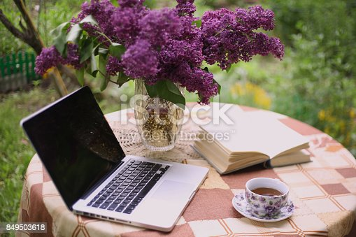 istock laptop, china teacup book and lilac bouquet in vase 849503618