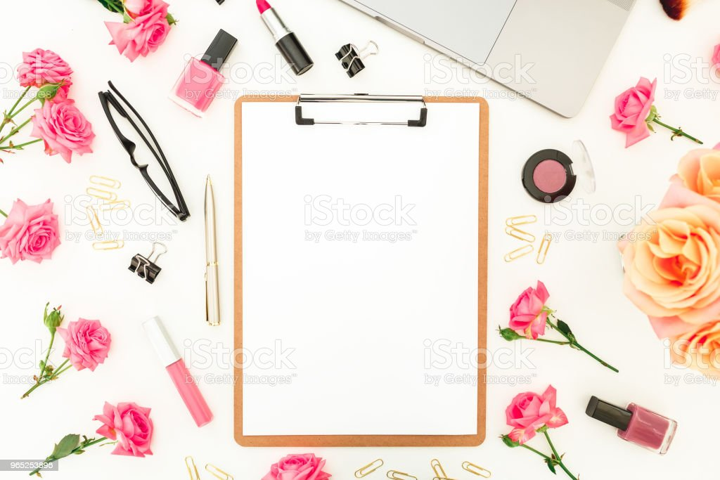 Laptop, clipboard, roses flowers, cosmetics and accessories on white background. Flat lay. Top view. Feminine office or blogger concept zbiór zdjęć royalty-free