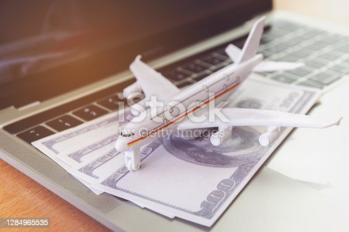 laptop computer and airplane and money on table. Online ticket booking concept