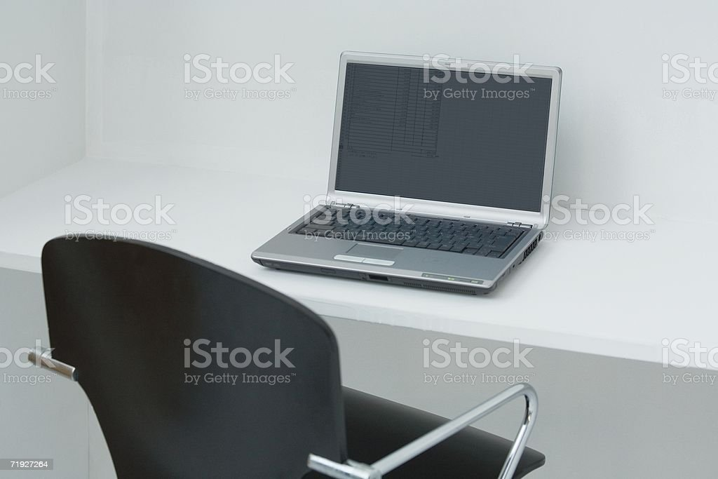 Laptop computer and an office chair royalty-free stock photo