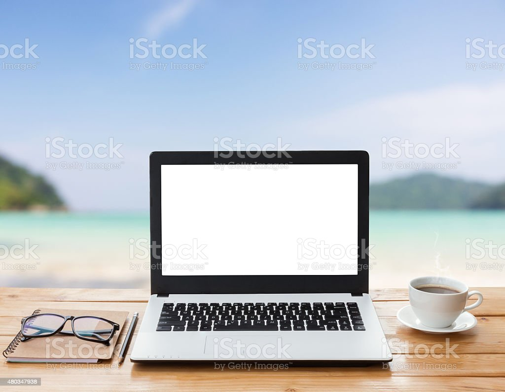 laptop computer and coffee on workspace beach background stock photo