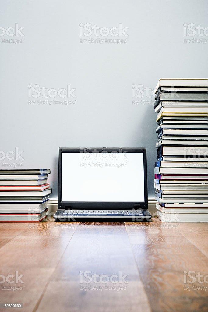Laptop computer between piles of books royaltyfri bildbanksbilder