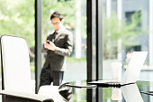 istock Laptop computer, digital tablet, and coffee on executive or manager table in modern office. Asian businessman or entrepreneur using smartphone in background. Business communication technology concept 812588382
