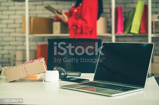 868776578 istock photo Laptop computer empty screen with shipping box in background 1252285379