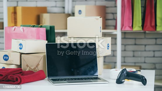 868776578 istock photo Laptop computer empty screen with shipping box in background 1256868730