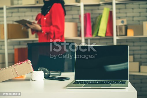 868776578 istock photo Laptop computer empty screen with shipping box in background 1259108031