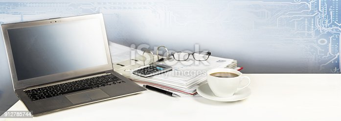 istock laptop computer, folder, calculator and a cup of coffee on a white office desk, digital business concept with copy space, panoramic banner format background 912785744