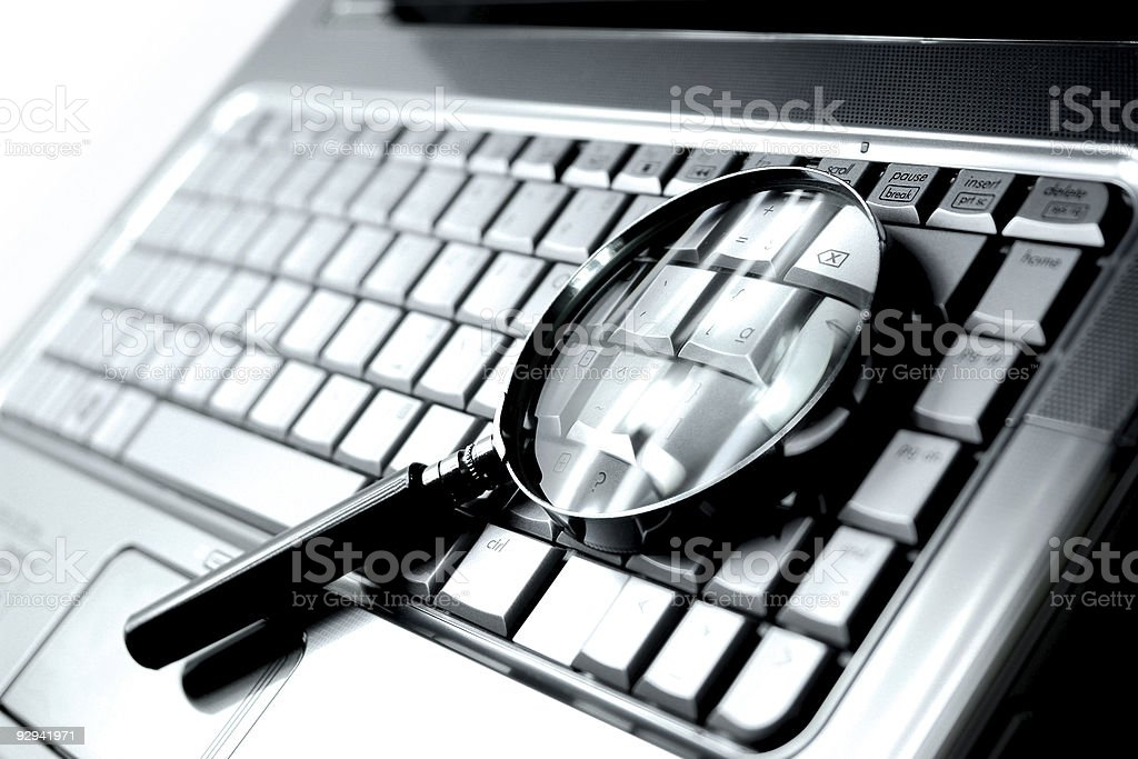 Laptop Computer + Magnifying Glass stock photo