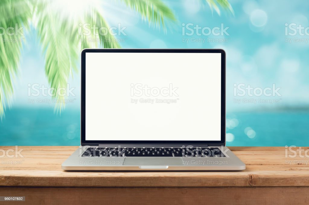 Laptop computer mock up over bokeh palm tree and tropical sea beach...