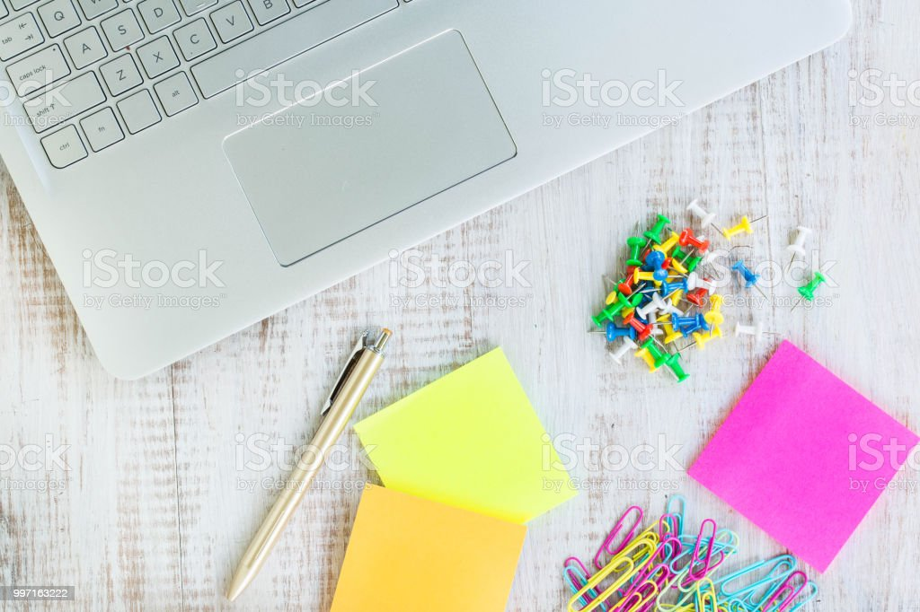 Laptop Computer On White Wood Desk With Push Pins Paper Clips and Post It Notes stock photo