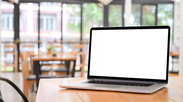 Laptop computer on wooden table with empty screen. stock photo
