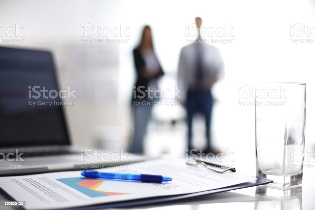 Laptop computer with folder on desk , two businesspeople standing in the background stock photo
