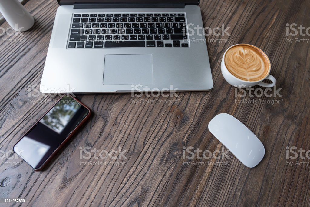 Laptop computer with latte art coffee on wooden table, Flat lay
