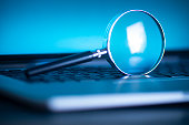 istock Laptop computer with magnifying glass as a symbol for searching information on the internet 1269819070