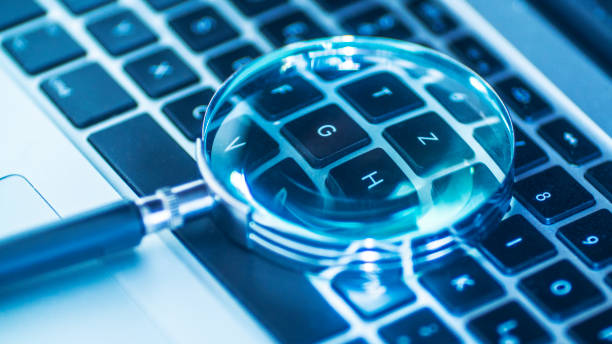 Laptop computer with magnifying glass as a symbol for searching information on the internet stock photo