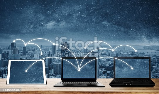 istock laptop computers with network connection and sharing data to other devices. Internet networking and connection 1145845402