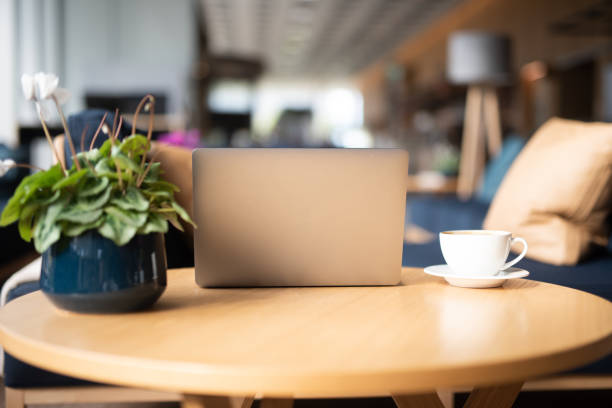 laptop, cup of coffee and flower on table. - coffee table imagens e fotografias de stock