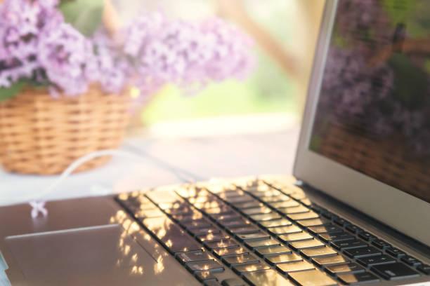 Laptop, Tasse Kaffee, Kekse und ein Korb mit lila Blumen auf einem weißen Holztisch in der Sommerterrasse - Konzept der Fernarbeit, Online-Geschäft, Selbstständigkeit – Foto